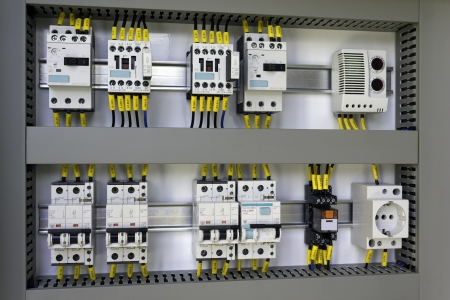 Industrial enclosure with electrical equipment: miniature circuit breakers, contactors, switches, relay, socket and thermostat.