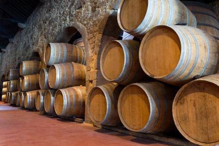 Row of wooden porto wine barrels in wine cellar (Porto, Portugal) Archivio Fotografico