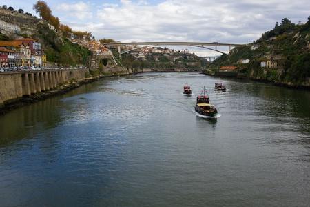 Porto city excursion boats on Douro river and Infante bridge (Portugal).