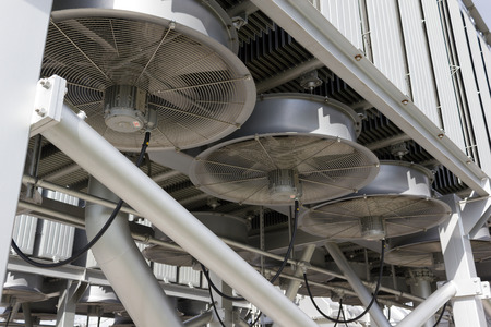 regulating: Industrial fans cooling an electrical power transformer. Stock Photo
