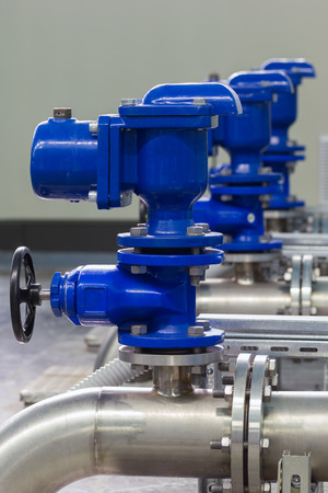 pumping: Industrial pipes and valves in water distribution process.