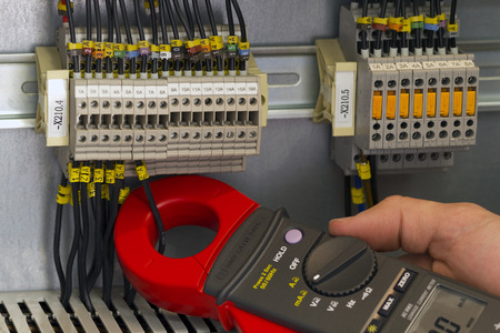 metro de medir: Ingeniero eléctrico de medir la corriente con pinza de corriente. Foto de archivo