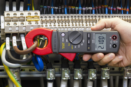 clamp: Electrician measuring current with current clamp.