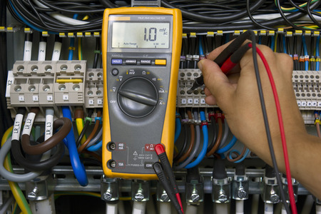 Electrician performing voltage measurements with electrical multimeter.