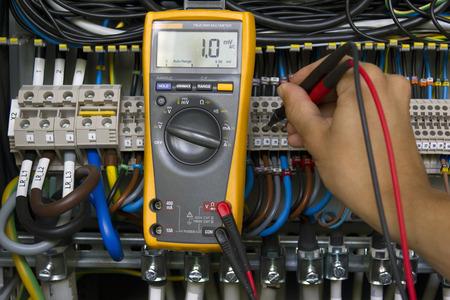 Elektricien presterende spanning metingen met elektrische multimeter.