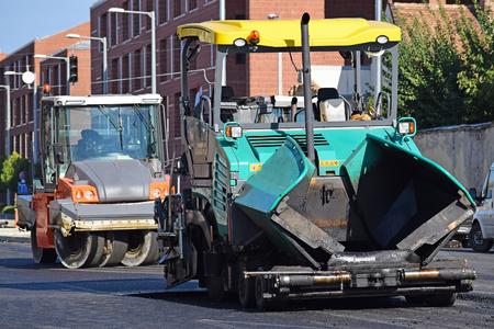asphalt paving: Asphalt paving vehicle and road roller at the road construction
