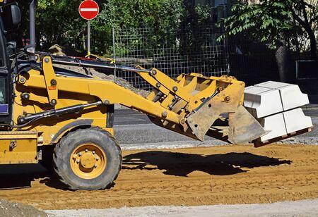 cargador frontal: pala cargadora trabaja en la construcci�n de carreteras Foto de archivo
