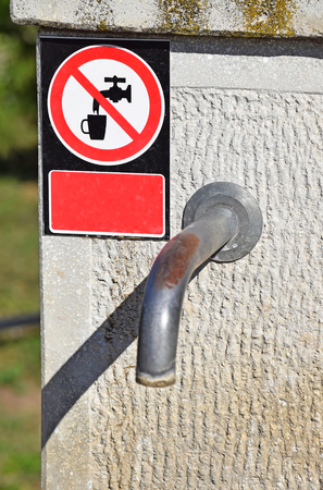 drinking water sign: Water tap with a not drinking water sign on the street in the city