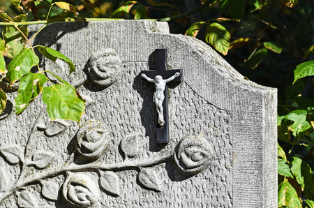 funeral: Cross and flower on the tombstone in the public cemetery