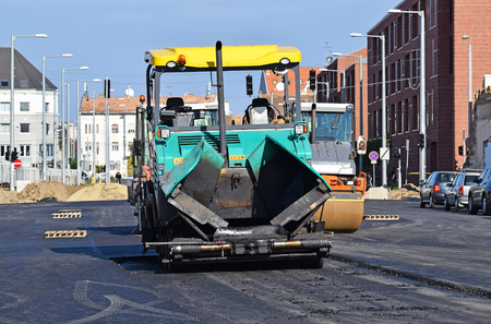 steam roller: Asphalt paving vehicle and steam roller at the road construction