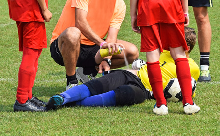 sports field: Injury on the soccer field, medic helps with a freezer spray Stock Photo