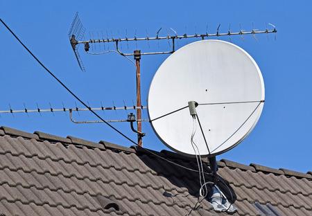 Satellietschotel en antenne op het dak van een gebouw