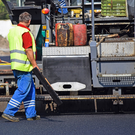 protective work wear: Construction worker at the road construction next to an asphalt paving vehicle Stock Photo