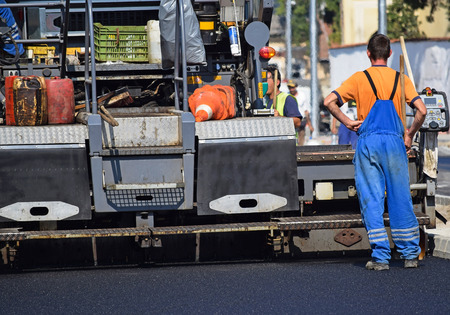 asphalt paving: Road construction with an asphalt paving vehicle in the city Stock Photo