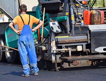 asphalt paving: Construction worker next to an asphalt paving vehicle at the road construction