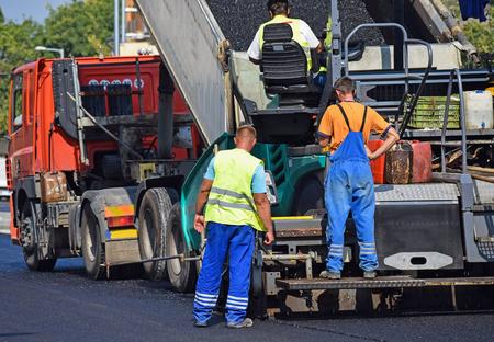asphalt paving: Asphalt paving vehicle at the road construction in the city