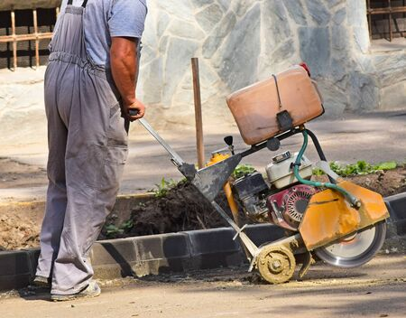 sawing: Construction worker is working with an asphalt sawing machinery