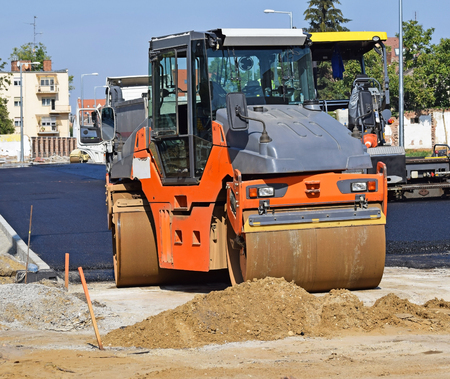 steam roller: Steamroller works at the road construction