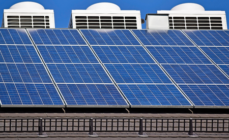 solar roof: Solar panels and air condiitioners on the roof of a building