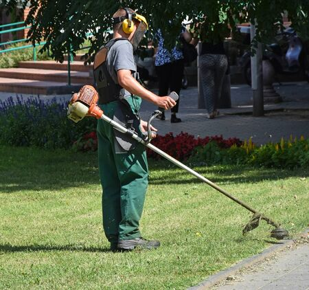 protective work wear: Man is mowing the grass in the park