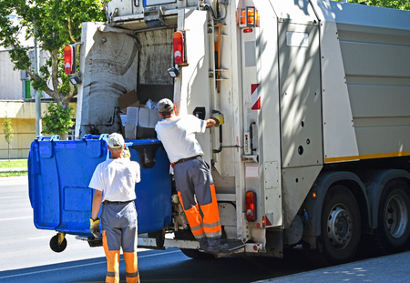 Garbage truck works in the city street