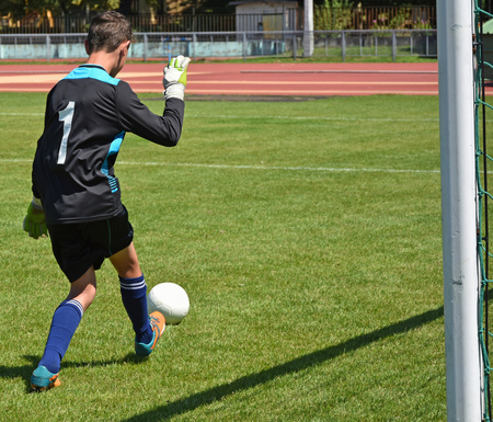 uniform green shoe: Young goalkeeper with a ball at the match