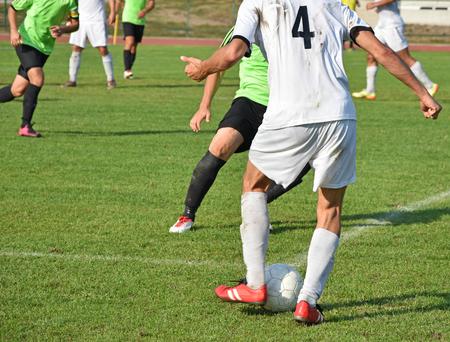 uniform green shoe: Soccer match outdoors in autumn