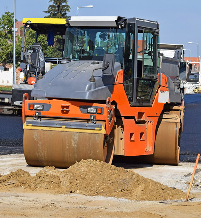 Steamroller works at the road construction