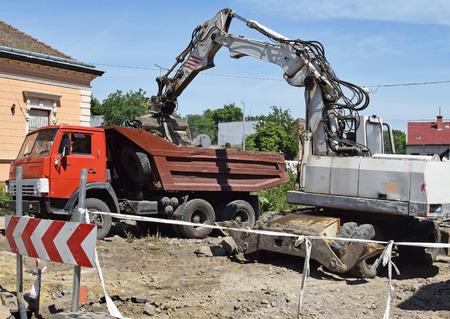 cargador frontal: Excavadora y camión en la construcción de carreteras Foto de archivo