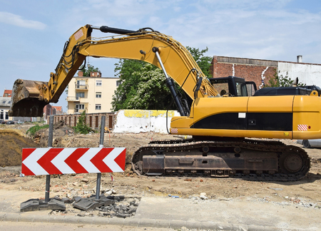 Excavator works at the road construction Stock Photo