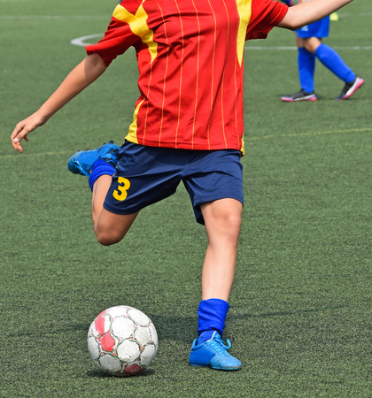 Young soccer player kicks the ball Stock Photo