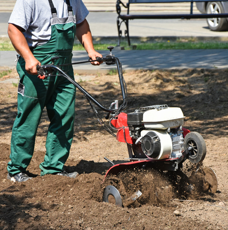 Gardener works with a tiller machinery