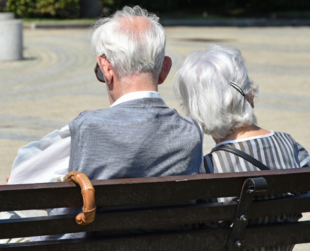 Old couple sits on a bench in the park