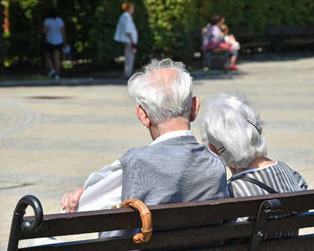Old couple sits on a park bench