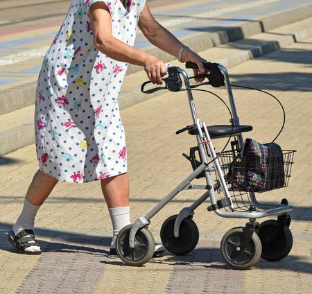 Alte Frau geht mit einem Spaziergänger Standard-Bild - 84950850