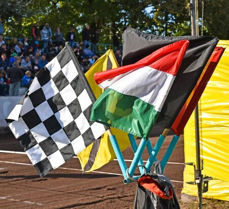 Flags of the speedway race next to the dirty track