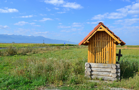 Wooden water well on the meadow, Romania Stock Photo