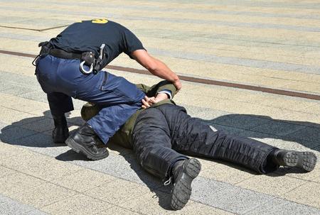 Un policier arrête un criminel dans la rue