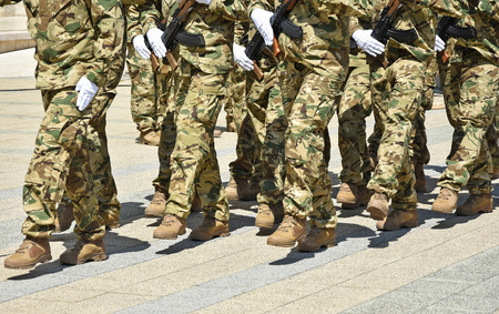Soldiers marching with machine guns Stock Photo