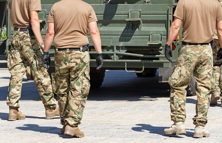 Soldiers next to a military truck vehicle Stock Photo