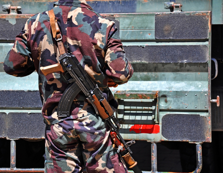 Soldier with machine guns outdoors