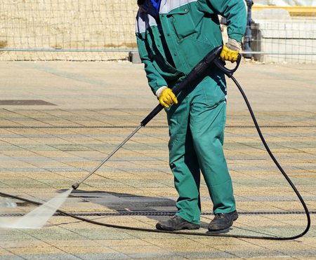 Street cleaning with a high pressure cleaner Stock Photo