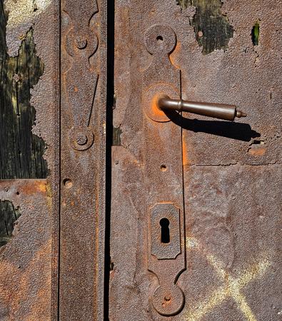 Old rusty metal door with handle