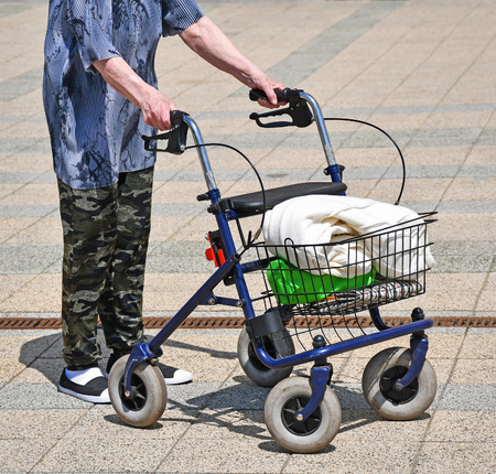 Old woman walks with a wheeled walker