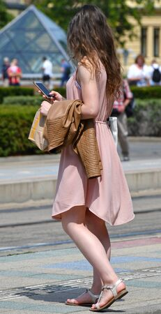 Pretty young women with smartphone in hand on the street