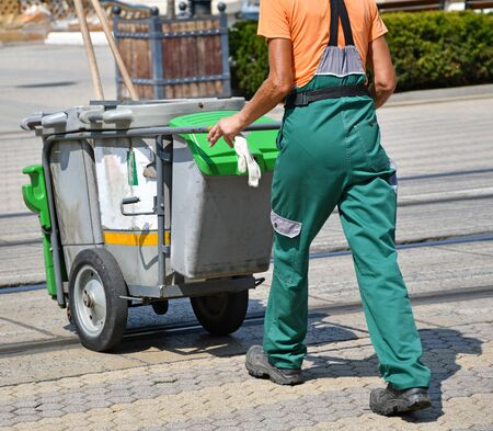 Street cleaner man with wheeled garbage cans