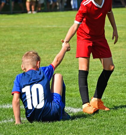 Young kid soccer player helps on the field Banque d'images