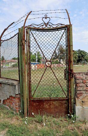 Old rusty metal door next to a ruined brick wall Banco de Imagens