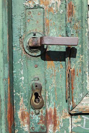 Door handle of a green wooden door Imagens - 131580569