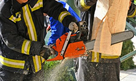 Firefighter works with a chainsaw outdoor